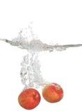 Respingo de duas maçãs na água fotografia de stock