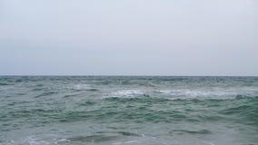 Respingo do pulverizador da onda sobre a praia no mar azul Onda macia no Sandy Beach Por do sol do mar filme