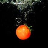 Respingo do tomate na água, Bacground preto Imagens de Stock