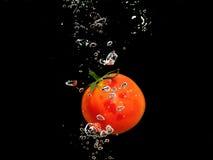 Respingo do tomate na água, Bacground preto Imagem de Stock Royalty Free
