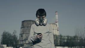 Respirateur de port de jeune garçon utilisant le téléphone portable contre des cheminées d'usine Concept de pollution atmosph?riq clips vidéos