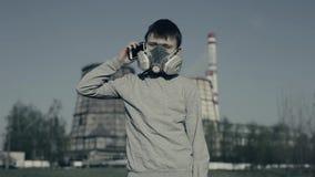 Respirateur de port de jeune garçon utilisant le téléphone portable contre des cheminées d'usine Concept de pollution atmosph?riq banque de vidéos