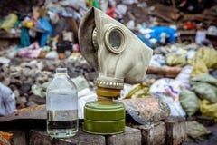 Respiratormaskering för gas på bakgrunden av avfall royaltyfria bilder