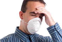 Respiratory Infection. A young man with a respiratory infection is wearing a mask to protect others and is suffering from a headache, isolated against a white Stock Image