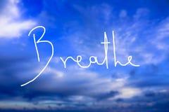 Respiri il logo scritto a mano nel cielo immagine stock libera da diritti