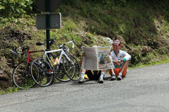 Respite moment. Beost,France,July 15th 2011:Image of two amateur cyclists taking a rest and reading L'Equipe magazine on the category H climbing route to the Stock Photography