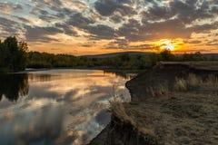 Resplandor de tarde del cielo nublado sobre River Valley con la reflexión de la puesta del sol en agua Imagen de archivo