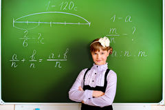 Respond. Smiling schoolgirl performs the task at the blackboard. Education Stock Photos