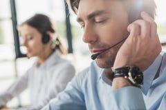 responsabile bello della call center in cuffie con il microfono che si siede nel luogo di lavoro mentre la sua seduta del collega fotografia stock