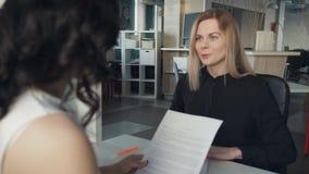 Responsabile che discute contratto con il cliente dentro l'ufficio video d archivio
