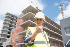Responsabile della costruzione che controlla progetto di costruzione sul sito Fotografia Stock Libera da Diritti