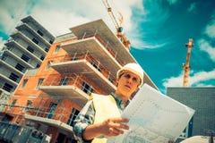 Responsabile della costruzione che controlla progetto di costruzione sul sito Fotografia Stock