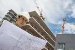 Responsabile della costruzione che controlla progetto di costruzione sul sito Fotografie Stock Libere da Diritti