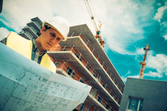 Responsabile della costruzione che controlla progetto di costruzione sul sito Immagini Stock Libere da Diritti
