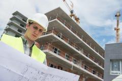 Responsabile della costruzione che controlla progetto di costruzione sul sito Immagini Stock