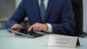 Responsabile di contabilità maschio che lavora al pc della compressa, al messaggio di battitura a macchina ed agli archivi di zum archivi video