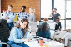Responsabile di ufficio con le cuffie che fanno le note Immagini Stock Libere da Diritti