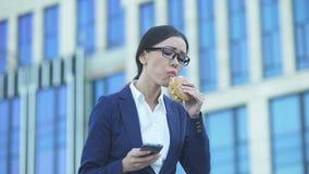 Responsabile di ufficio femminile che mangia hamburger non sano che controlla i messaggi sul telefono, sforzo video d archivio