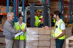 Responsabile e lavoratori del magazzino che preparano una spedizione Fotografia Stock Libera da Diritti