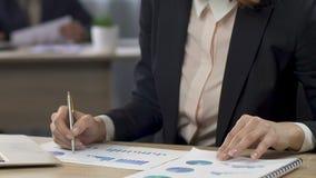 Responsabile femminile che confronta due grafici e che fa le note all'ufficio, affare stock footage