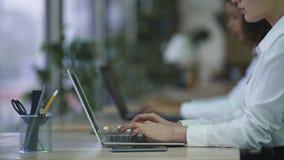Responsabile femminile che lavora al computer portatile al centro di sostegno della società, contattante i clienti stock footage