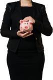 Responsabile femminile che tiene un porcellino salvadanaio Fotografia Stock