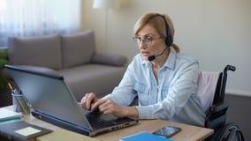 Responsabile femminile disabile che si siede alla scrivania, lavorante al computer portatile dalla casa video d archivio
