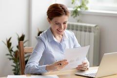 Responsabile femminile esecutivo che analizza il grafico di statistiche di vendite fotografia stock