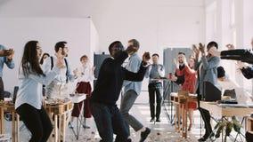 Responsabile maschio africano millenario di divertimento felice che celebra successo di carriera dell'ufficio con il ballo di div video d archivio