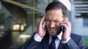 Responsabile maschio sovraccaricato che parla sul telefono, soffrente dall'emicrania, emicrania fotografie stock libere da diritti