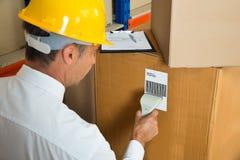 Responsabile Scanning Cardboard Box con il lettore di codici a barre Immagini Stock
