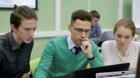 Responsabili di collaborazione su un nuovo progetto di affari Giovani che lavorano insieme ad un computer portatile Raggiungiment video d archivio
