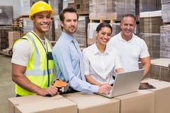 Responsabili e lavoratore del magazzino che esaminano macchina fotografica Fotografia Stock