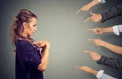 Responsabilizando o Mulher irritada ansiosa julgada pelos povos diferentes que apontam as mãos dos dedos nela Fotos de Stock Royalty Free