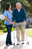 Responsable aidant l'homme aîné avec la trame de marche Photos libres de droits