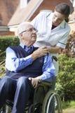 Responsable poussant l'homme aîné dans le fauteuil roulant Images stock