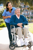 Responsable poussant l'homme aîné dans le fauteuil roulant Photo stock
