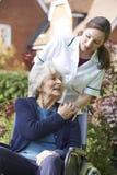 Responsable poussant le femme aîné dans le fauteuil roulant Images libres de droits