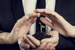 Responsibility, protection and teamwork concept. Female hands shielding a green sprout growing from a fertile black soil held by male hands Stock Images