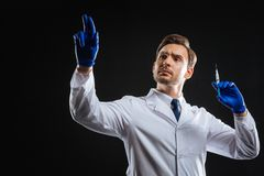 Responsible attentive medic holding a syringe lifting his hand. Correct dose. Responsible attentive qualified medic spending time in the dark room holding a Royalty Free Stock Photography