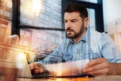 Responsible designer looking at the screen while reading emails. Answering emails. Calm qualified responsible designer sitting at the table with documents in his Royalty Free Stock Photo