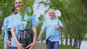 Responsible eco activists walking park path holding green tree saplings shovel stock footage