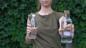 Responsible lady choosing reusable glass bottle instead of plastic, save planet