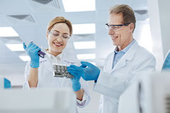 Responsible medical worker doing blood test. May I help you. Delighted male person keeping smile on his face stretching left hand while looking at his colleague royalty free stock photo