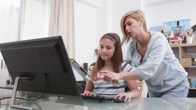 Responsible mother helping her daughter to finish the homework stock video footage