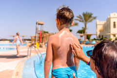 Responsible mother rubbing sunscreen on her son Stock Photo