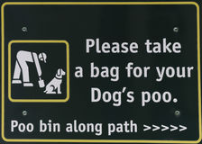 Responsible pet ownership. An informational sign instructing people to please take a bag for their dogs poo to ensure a clean environment, conceptual of Royalty Free Stock Photos