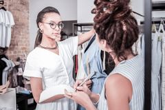 Diligent responsible trainee with hair bun listening attentively to fashion designer. Responsible trainee. Diligent responsible trainee with hair bun listening royalty free stock photography