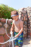 Responsible young boy rinsing off his shoes Royalty Free Stock Photos