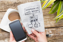 Responsive web design. Web designer holding a blueprint of a new mobile application. Responsive web design concept Royalty Free Stock Photos